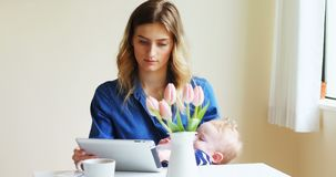 Mother using digital tablet while feeding her baby 4k. Mother using digital tablet while feeding her baby at home 4k stock footage