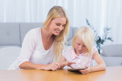 Mother using digital tablet with her daughter Royalty Free Stock Photo