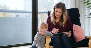 Mother using digital tablet while tacking care of her baby 4k. Mother using digital tablet while tacking care of her baby in living room 4k stock video footage