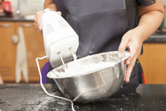 Mother using electric mixer to mix ingredients of sponge cake. In kitchen royalty free stock images