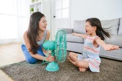 Free Mother Using Fan Let Daughter Enjoying Cool Wind Stock Photos - 97172653