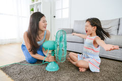 Mother using fan let daughter enjoying cool wind. Beautiful mother using electric fan let pretty little daughter enjoying cool wind and eliminate summer hot in Stock Photos