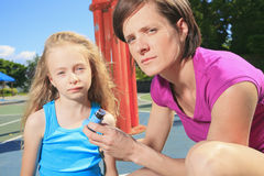 Mother using inhaler with her asthmatic daughter Royalty Free Stock Image