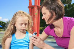 Mother using inhaler with her asthmatic daughter Stock Photography