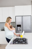 Mother using laptop while carrying baby in kitchen Stock Images