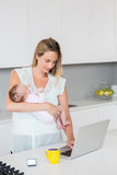 Mother using laptop while carrying baby in kitchen Stock Photos