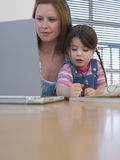 Mother Using Laptop While Daughter Coloring At Table. In house Stock Images