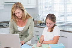 Mother using laptop while daughter doing homework Royalty Free Stock Image
