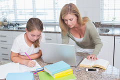 Mother using laptop while daughter doing homework Royalty Free Stock Photo