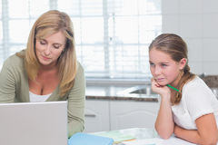 Mother using laptop while daughter doing homework Stock Image