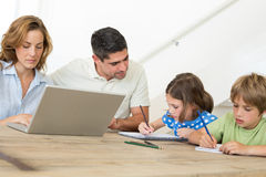 Mother using laptop while father assisting children in coloring Stock Image