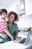 Mother using laptop with son in kitchen Stock Photography