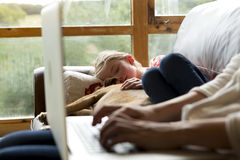 Mother using laptop whilst daughter sleeps Stock Photo