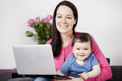 A mother using a laptop whilst holding her baby son on her lap Stock Photo
