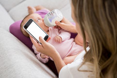 Mother using mobile phone while feeding her baby with milk bottle. At home Royalty Free Stock Images