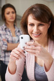 Mother Using Mobile Phone With Frustrated Teenage Daughter Royalty Free Stock Images