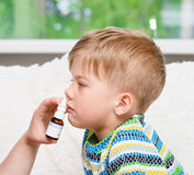 Mother using nose spray to cure her little boy. Focus on hand Royalty Free Stock Images