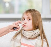 Mother using nose spray to cure her teen girl Royalty Free Stock Photography