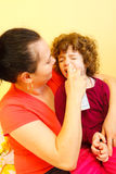 Mother using spray to cure. Caring mother clearing her daughter's nose with spray Royalty Free Stock Photos
