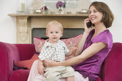 Mother using telephone in living room with baby Royalty Free Stock Images