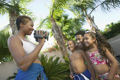Mother Videotaping Family in swim wear in back yard side view Royalty Free Stock Photography