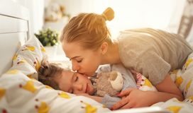 Mother wakes her daughter in bed in  morning Royalty Free Stock Photo