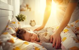 Mother wakes up sleeping child daughter girl in morning. Mother wakes up sleeping child daughter girl in the morning Royalty Free Stock Photo