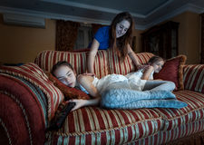 Mother waking up two daughter fell asleep at night while watchin Royalty Free Stock Images