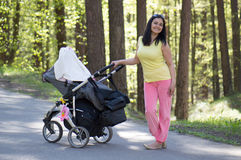 Mother at walk with carriage Stock Photos