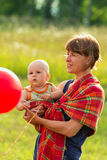Mother on walk with the small child in ringsling Stock Images