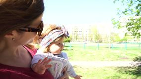 Mother walking with baby girl in the park stock video
