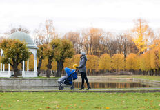 Mother walking with a baby pram in the park Stock Image