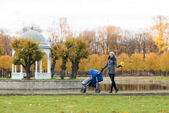 Mother walking with a baby pram in the park Royalty Free Stock Images