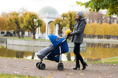 Mother walking with a baby pram in the park Royalty Free Stock Photography