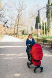 Mother walking with baby stroller Royalty Free Stock Photos