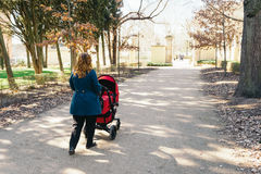 Mother walking with baby stroller Royalty Free Stock Image