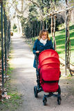 Mother walking with baby stroller Stock Photos