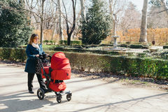 Mother walking with baby stroller Stock Images