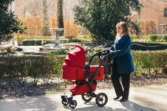 Mother walking with baby stroller Royalty Free Stock Photography