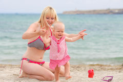 Mother is walking on beach with her little baby girl daughte Royalty Free Stock Image