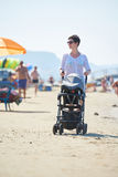 Mother walking on beach and push baby carriage Stock Photo