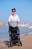 Mother walking on beach and push baby carriage Stock Image