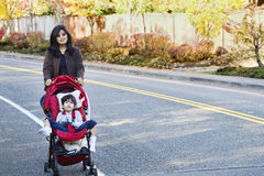 Mother walking with disabled son in stroller o. Mother walking with her disabled son in stroller outdoors Royalty Free Stock Photos
