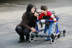Mother walking with disabled son in walker. Mother with disabled son walking outdoors with walker, medical mobility equipment Royalty Free Stock Photo