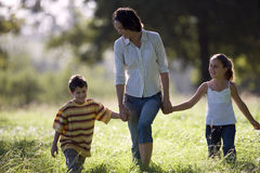 Mother walking hand in hand with son (6-8) and daughter (7-9) in field, front view Stock Photography