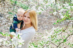 Mother walking with her baby son in garden of blooming magnolias Stock Image