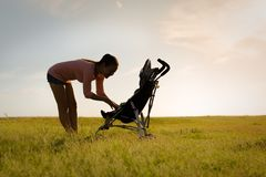 Mother walking her baby in stroller, outside at a beautiful park during sunset stock photography