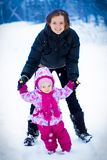 Mother walking with her little daughter in winter Stock Photo