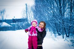 Mother walking with her little daughter in winter Stock Photos