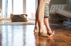 Mother walking at home with child standing on her feet Stock Photo